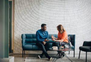 Canapé bleu avec un homme et une femme en train de discuter durant une pause