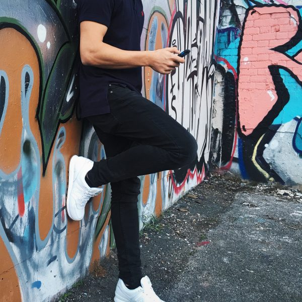 homme en basket blanches adossé à un mur taggé