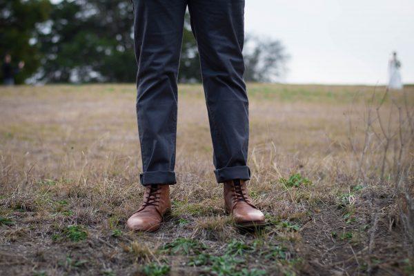vue sur les jambes d'un homme portant un pantalon gris foncé et des bottines marron