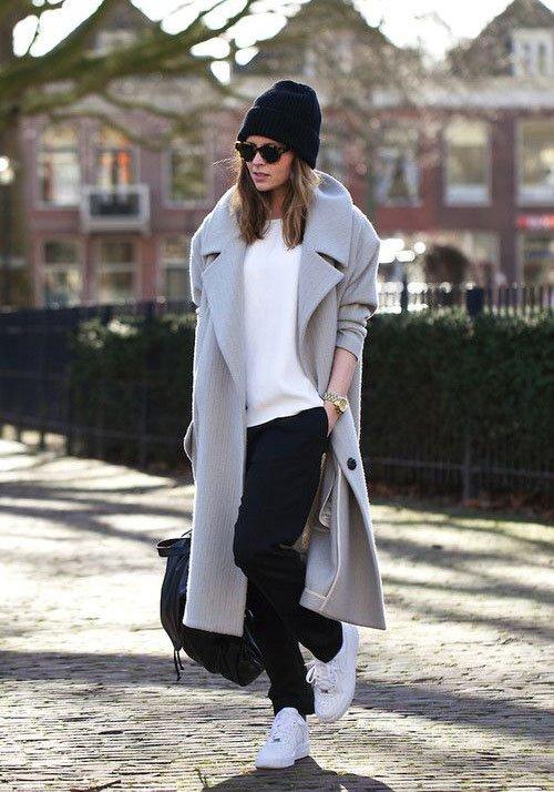 femme portant un jogging foncé, un haut blanc un manteau gris et des baskets blanches avec un bonnet noir et des lunettes de soleil
