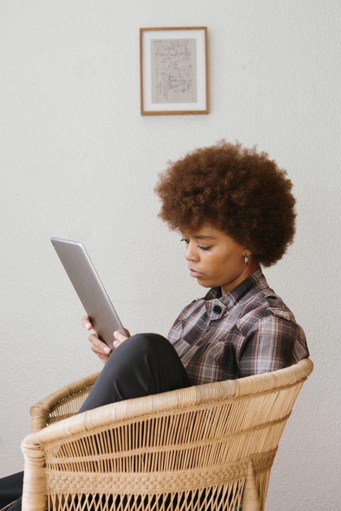 Jeune femme assise dans un fauteuil qui lit sur une tablette
