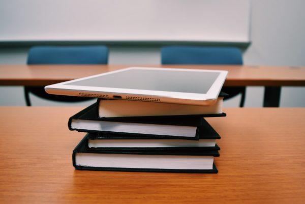 Tablette posée sur une pile de livres