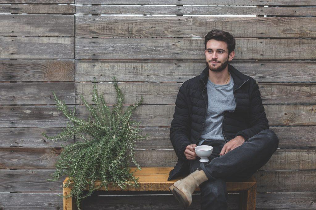 jeune homme assis avec une tasse à la main portant un jean foncé un t shirt gris des boots marron et une doudoune noire