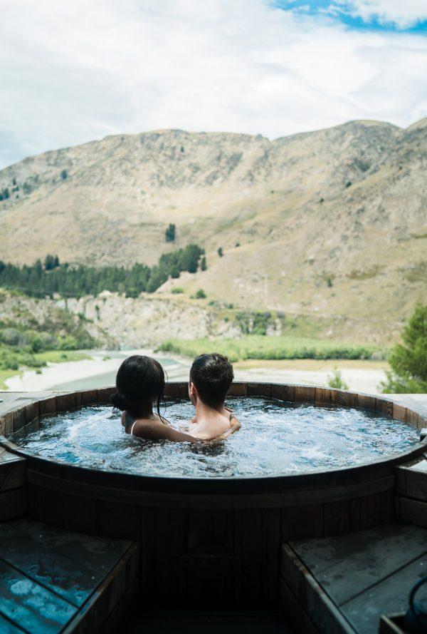 deux personnes dans un spa extérieur rond en bois